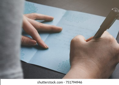 Lady writing a hand crafted card to family or friend. View over her shoulder. Close up of card and hands. Concept.