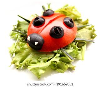 Ladybug made of raw tomato on lettuce leaf