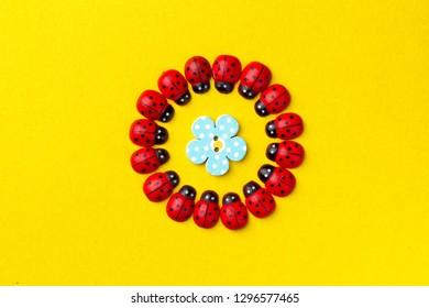 Ladybugs among a decorative flower on yellow background