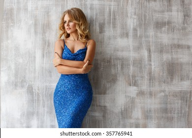 Ladylike woman in the blue evening sparkling dress is posing near the light texture wall