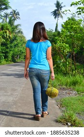 Lady's back walking in countryside with Durian fruit hanged in a rope