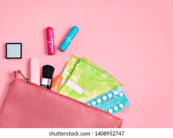Lady's bag. Sanitary pads and tampons in cosmetic bag on pink background. Concept of critical days, menstruation