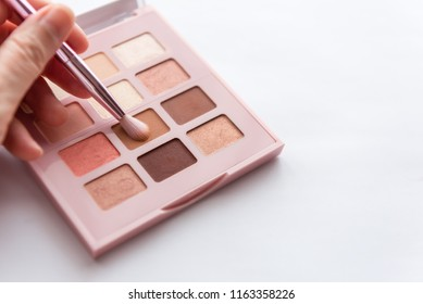 lady's hand holding make up brush dipping into peach brown eye shadow palette