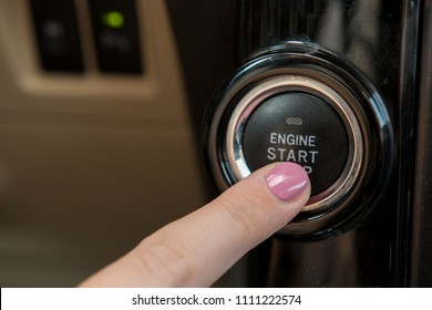 Lady's hand pressing on car's engine start button.