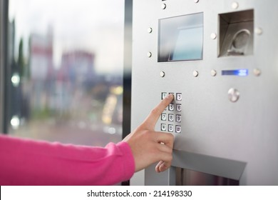 Lady's hand using a dial pad on a vending machine. The fore finger is placed on the dial pad key.