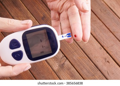 a lady's hands measuring blood sugar, glucose with a home test to control her diabetes