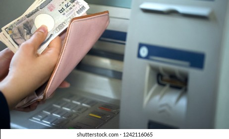 Ladys hands putting Japanese Yen in wallet, cash withdrawn from ATM, travelling