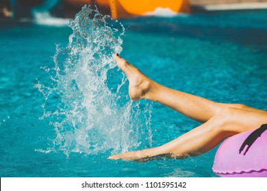 ladys slim and soft legs on the inflatable ring playing with water in the swimming pool. Summer Vacation. Enjoying suntan. Weekend on resort