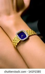 lady's wrist wearing gold and diamond  watch