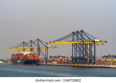Laem Chabang seaport, Thailand - March 17, 2019: Large Hapag-lloyd blue container ship worked by tall blue and yellow cranes under sunset sky. Deck of vessel full of colorful boxes.