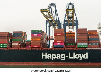 Laem Chabang, Thailand - March 16, 2019: Container port and terminal and mid section of Hapag Lloyd ship under gray sky. Two yellow cranes loading and unloading it. Colored container stacks on ship.