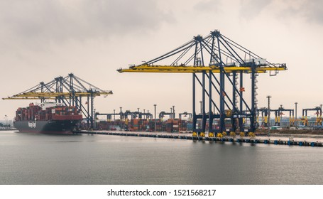 Laem Chabang, Thailand - March 16, 2019: Entering Container port and terminal from the sea under gray cloudscape. Yellow cranes and Hapag Lloyd ship on dock with four cranes working it.