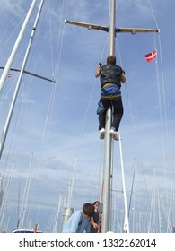 Laeso island, Denmark - July 18, 2011: The audacious sailor climbing to the top of mast to repair yacht equipment