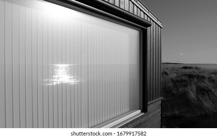 Laesoe / Denmark: The April evening sun reflects in the window pane of a modern holiday house in the dunes
