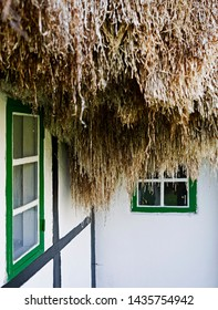 Laesoe / Denmark: Eaves of an old half-timbered farmhouse with green window frames and thatched with a seaweed roof