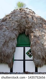 Laesoe / Denmark: Front side of an old half-timbered cottage with seaweed roof