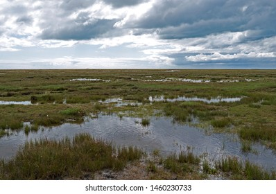 "Laesoe / Denmark: Impressive cloudscape over the flat and wide salt marsh with tidal creeks and lakes on ""Hornfiskroen"" in the south of the Kattegat island"
