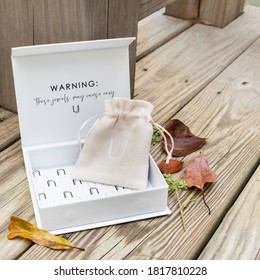 LAFAYETTE, L.A. / USA - SEPTEMBER 19, 2020: Uncommon James, accessory gift box, with logo tissue paper, and a small jewelry bag inside, on a wood textured background.