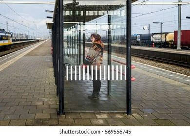 LAGE ZWALUWE, THE NETHERLANDS – JANUARY 29: Woman waiting at the station until the train arrives on January 29, 2017