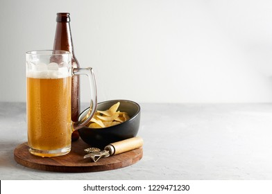 Lager beer in glass and bottle with potato chips on gray concrete background. Close up view with copy space