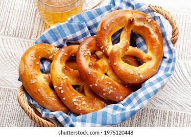 Lager beer mug and fresh baked homemade pretzel with sea salt on wooden table. Classic beer snack - Shutterstock ID 1975120448