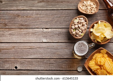 Lager beer mug and snacks on wooden table. Nuts, chips. Top view with copyspace