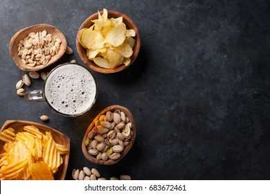 Lager beer mug and snacks on stone table. Nuts, chips. Top view with copyspace