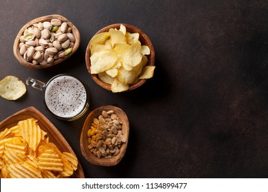 Lager beer and snacks on stone table. Nuts, chips. Top view with copyspace