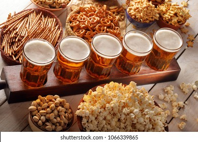 Lager beer and snacks on wooden table with copy space