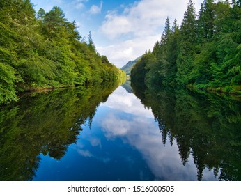 Laggan, UK - September 6, 2019: Laggan Avenue on the Caledonian Canal in Scotland, UK - on a calm, sunny day the sky and trees are reflected in the calm water of the canal.