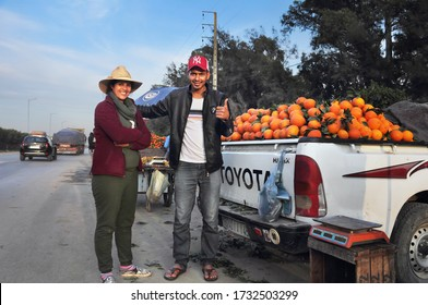 LAGHDIR, MOROCCO - FEB 06: Unidentified morrocan man and woman sale oranges on the road and pose for a camera on February 06, 2020 in Laghdir, near Chaouen, Morocco, Maghreb, North West Africa