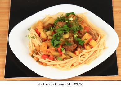 Lagman is a national Central Asian dish on a white plate and a black tray