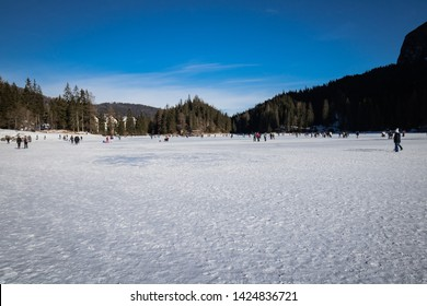 Lago di Braies, Italy - January 1, 2019: people having fun ice skating and hiking on frozen lake lago di braies for the first day of new year