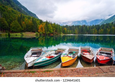 Lago di Fusine the mountain lake at boat and Mangart mountain in the background in north Italy alps, Europe