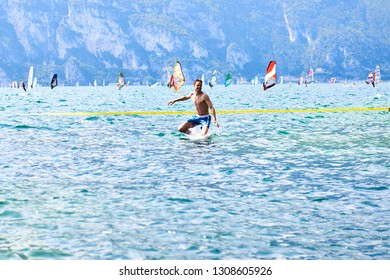 LAGO DI GARDA / ITALY - AUGUST 16, 2014: Slackliner slacklining above the water at stunning beach of Lake Garda. Portrait of a Mindfulness Slackliner Man Crossing a Tightrope