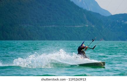 Lago di Santa Croce/Belluno/Veneto/Italy - 1 August 2018: The Lago di Santa Croce is a semi-natural lake. Kitesurfing Kiteboarding action photos man among waves quickly goes.