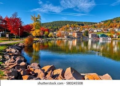 Lago di Serraia (Serraia lake), Colorful leaves on trees along lake in autumn and the small town of Baselga di Pine, Trentino Alto Adige, Italy