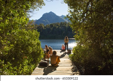 LAGO ESCONDIDO, BARILOCHE - ARGENTINA - FEBRUARY 2017 - Unidentified young people, enjoying the summer on the patagonian lake, eating and having fun on the deck.