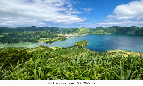 Lagoa Verde and Lagoa Azul, two adjacent lakes in wide volcanic crater called Sete Cidades, filled by tropical greenery, located on Sao Miguel island of Azores, Portugal.