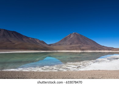 Lagoon with birds and pelicans with colorful mountains. Landscape of the Salar de Uyuni and lagoons like Laguna Verde or Laguna Colorada in the national park in Bolivia.