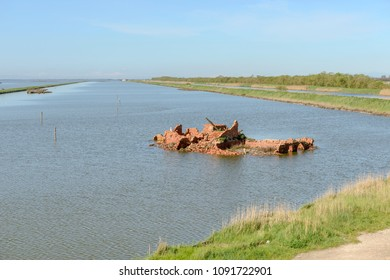 lagoon view with ruins of bricks building on small island, shot in bright spring sun light at Comacchio, Ferrara,  Italy