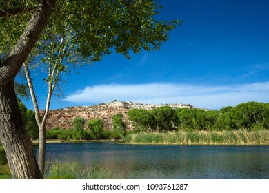 Lagoon with water, marsh, trees, and cliffs in spring at Dead Horse Ranch State Park