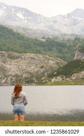 Lagos de Covadonga, Asturias, Spain. 6/22/15. A girl wearing blue shorts and a grey jumper stands in front of a lake in Asturias, north of Spain, with mountains in the background.