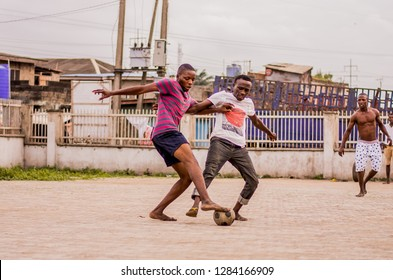 LAGOS, NIGERIA- AUGUST 8, 2016: Young men play the game of football in their neighbourhood, in Lagos Nigeria.