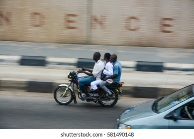 Lagos, Nigeria - September 13, 2016: Motorcycle rider also known as Okada rides through independence tunnel in Maryland with two passengers on board.