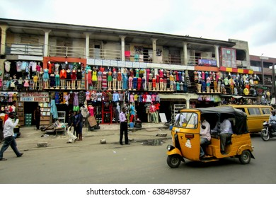 LAGOS, NIGERIA - SEPTEMBER 4, 2012: Colorful african fashion shops, with many clothes hanging in mannequins, in the large city of Lagos, Nigeria