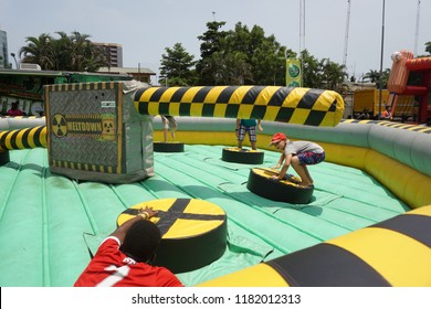 Lagos/Nigeria-April 16th, 2016: A group of children playing on the inflatable sweeper twister game at a carnival. Player hit by the rotating pole will be eliminated. Made famous by Wipeout franchise.