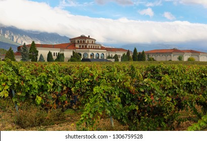LaGuardia, Spain - October 18, 2018: Entrance to the wine cellars of La Rioja called Campillo wine cellar. The vineyards are in autumn colours with the colonial building outstanding at background.