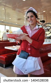 LAGUNA BEACH, CALIFORNIA / USA - JANUARY 28 2010: A smiling waitress in a red and white striped uniform and white cap delivers an order of  hamburger and french fries at 1950s-style Ruby's AutoDiner.