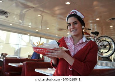 LAGUNA BEACH, CALIFORNIA / USA - JANUARY 28 2010: Young waitress in a red and white striped uniform and white cap delivers an order of  hamburger and french fries at 1950s-style Ruby's AutoDiner.